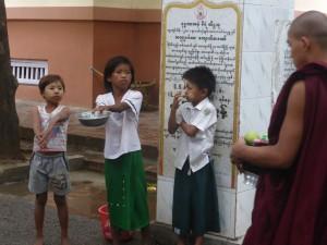 托鉢から帰って来た僧侶におねだりする子供達