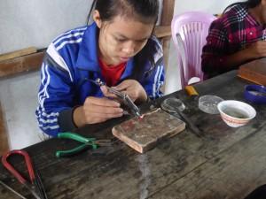 工房で工芸品を加工する銀細工職人