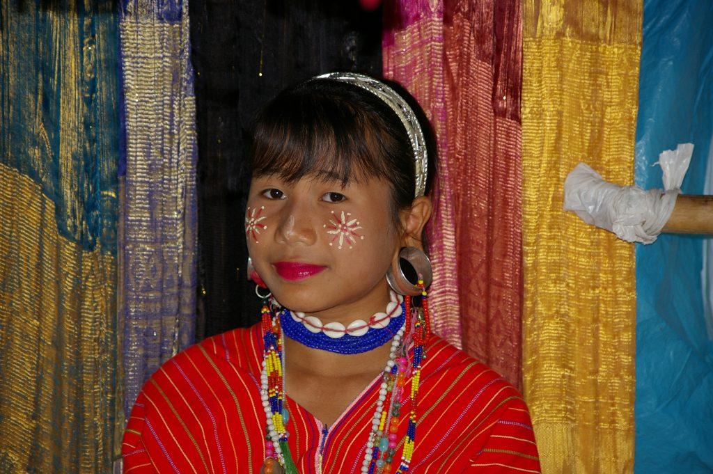 巨大ピアスを装着しフェースペイントをしているカレン族の若い女性